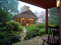 A Magical RefugeRustic outdoor fireplace beckons across a lush drizzly Courtyard - Restored  Abiah Taylor House  West Chester PA John Milner Architects