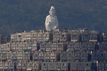 A -meter-high -foot Buddhist Avalokitesvara or Guan Yin statue part of the Tsz Shan Monastery stands behind luxurious houses at Tai Po District in Hong Kong Bobby Yip