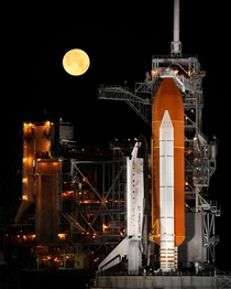A nearly full Moon sets as the space shuttle Discovery sits atop Launch pad A at the Kennedy Space Center in Cape Canaveral Florida Wednesday March   Photo Credit NASABill Ingalls