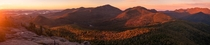 A panorama of the sunrise on Dix Mountain and the Adirondack Great Range from the summit of Noonmark Mountain NY USA