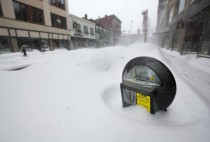 A parking meter pokes out of a snow bank during a blizzard in Portland Maine