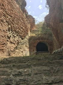 A partially collapsed staircase leading to spectator seats at the Flavian Amphitheater of Pozzuoli the third-largest Roman arena in Italy The arch below supports a passageway now exposed by damage The complex based on the Colosseum was constructed by Vesp