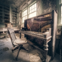 A partially stripped piano in an abandoned asylum
