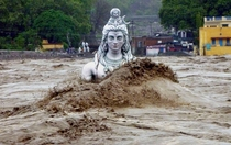 A partially submerged statue of Shiva stands in the flooded River Ganges in Rishikesh in the northern Indian state of Uttarakhand June