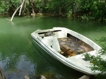 A peaceful abandoned fishing boat on a river in San Marcos TX
