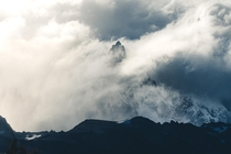 A peak in Patagonia breaks out amid the clouds