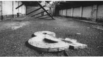 A photo taken in an abandoned factory in my town called the Irish Oil amp Cake Mills where its ampersand lies forlorn The building has since been demolished and replaced with the car park of a shopping centre