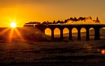 A preserved British steam locomotive travelling over Ribblehead Viaduct England x-post from rtrains