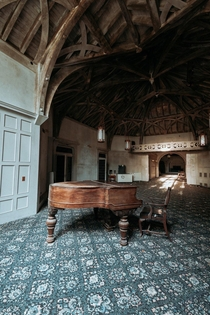 A -room mansion sitting abandoned in New York State this is the piano room during sunset