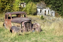 A rusty old car sits along Main Street in Marysville Montana