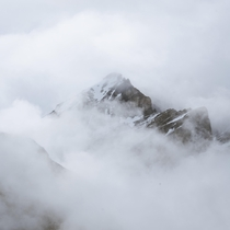 A sea of clouds engulfing a mountain peak in Banff National Park