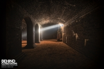 A single beam of light penetrates the darkness in an abandoned Victorian underground reservoir