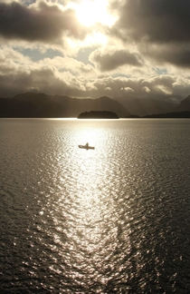 A single canoeist in the sunlight at Derwent Water The Lake District
