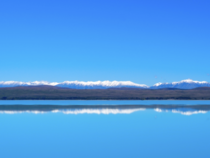 A slice of mountain cuts through the blue of sky and lake - Lake Pukaki New Zealand
