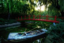 A small red bridge in the Forbidden City with boat