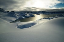 A soft layer of untouched snow next to the frozen sea on Kulusuk Island by eastern Greenland