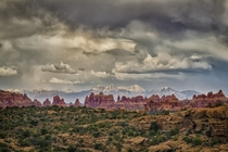 A storm brews over the Needles district of Canyonlands NP with the La Sal Mountains in the distance  photo by Mark Betts