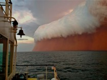 A storm formation tinged with red dust travels across the Indian Ocean near Onslow on the Western Australia coast on January