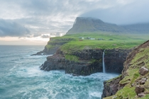 A storm rolling in over Mulafossur Falls in the Faroe Islands