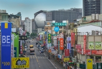 A street with many signs in Taipei Taiwan with the Taipei Performing Arts Center in the background