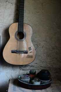 A table and a guitar in an abandoned house