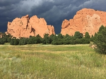 A thunderstorm approaches the sunlit sandstone of the Garden of the Gods in Colorado