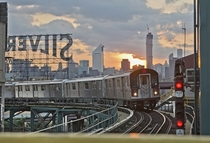 A  train moving into Queensboro Plaza with the Manhattan skyline in the background