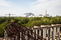 A view of the Chernobyl Nuclear Power Plant From the right Reactors  and  are located beneath the black cubes on the roof of the building  the destroyed Reactor Block  on the left is now covered by the New Safe Confinement Taken from the rooftop of the un