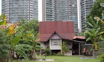 A village in the city - a traditional Malay house in Kampong Bharu New Village overshadowed by high-rise apartment towers in Kuala Lumpur Malaysia