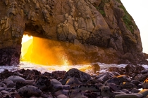 A winter portal the sunset light through the keyhole in the rock at Pfeiffer Beach Big Sur California