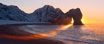 A winter sunrise through Durdle Door Dorset UK by Alistair Haimes