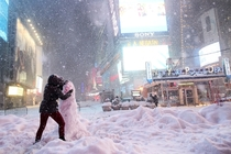 A woman decorates a snowman in Times Square as all cars but emergency vehicles are banned from driving on the road on January   Yana Paskova