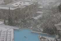 A woman swims in the pool at the David Citadel Hotel during a snow storm in Jerusalem