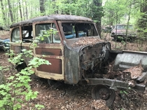 A woodie wagon of unknown make rotting away in an abandoned junkyard