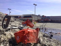 Abandoned Asian supermarket its parking lot a dumping ground for a melting mountain of snow and mangled shopping carts left over from Bostons  record snowfall