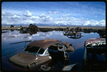 Abandoned automobiles and other debris clutter an acid water and oil filled five acre pond Near Ogden Utah