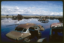 Abandoned automobiles and other debris clutter an acid water- and oil-filled five-acre pond Ogden Utah