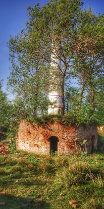 Abandoned brick furnace near a fully constructed abandoned brick furnace with  meter tower