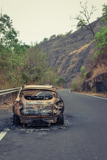 Abandoned burnt car in a mountain pass