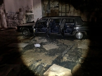 Abandoned Cadillac limousine inside of an decrepit store x