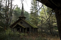 Abandoned church in the woods with a mossy rooftop and steeple Photo by Robert Wirth