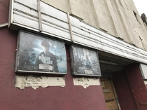 Abandoned cinema with movie posters still outside - Derbyshire England