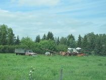 Abandoned farm equipment rotting away in a field