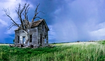 Abandoned Farmhouse with rain in the distance WesternCentral Kansas