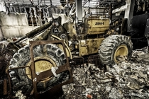 Abandoned front end loader rusting away inside a burnt out heavy equipment repair shop