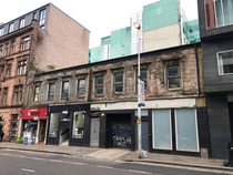 Abandoned house in Glasgow with stores in ground floor still open