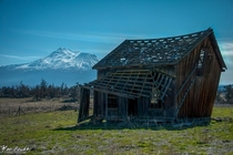 Abandoned house on an old nature conservancy with Mount Shasta in the distance