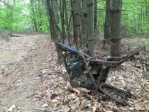 Abandoned motorcycle on the side of a motocross trail in the woods OC