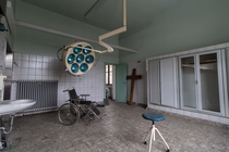 Abandoned operating theatre with wheelchair and surgical lamp