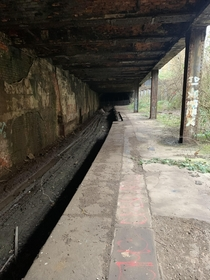 Abandoned railway line and platform with a fenced off tunnel near Glasgow City Centre